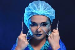 Strumenti del dentista a disposizione del dentista Woman di modo nella tonnellata blu di colore Fotografia Stock