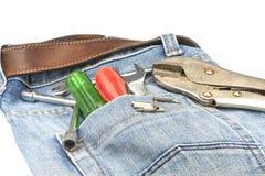 Strumenti del lavoro dentro con le blue jeans immagini stock