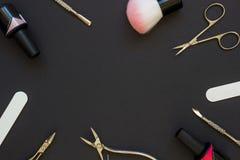 Strumenti del manicure sui precedenti scuri Immagine Stock