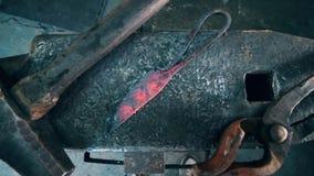 Strumenti del metallo che si trovano su una grande incudine ad una forgia stock footage