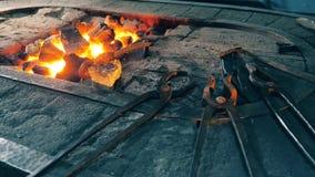 Strumenti del metallo che si trovano vicino al fuoco ad una forgia archivi video