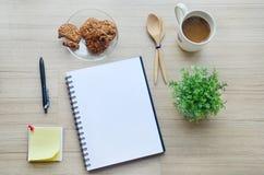 Strumenti della carta in bianco, della pausa caffè e dell'ufficio sulla tavola di legno - T Fotografie Stock