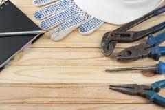 Strumenti della costruzione, guanti bianchi del casco, del blocco note e del lavoro su fondo di legno Copi lo spazio per testo Fotografia Stock