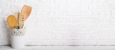 Strumenti della cucina, tagliere verde oliva su uno scaffale della cucina contro un muro di mattoni bianco Fuoco selettivo Immagine Stock