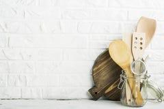 Strumenti della cucina, tagliere verde oliva su uno scaffale della cucina contro un muro di mattoni bianco Fuoco selettivo Fotografia Stock Libera da Diritti