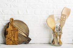 Strumenti della cucina, tagliere verde oliva su uno scaffale della cucina contro un muro di mattoni bianco Fuoco selettivo Fotografia Stock