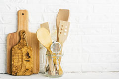 Strumenti della cucina, tagliere verde oliva su uno scaffale della cucina contro un muro di mattoni bianco Fuoco selettivo Immagini Stock