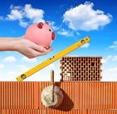 Strumenti della muratura su un muro di mattoni e su una mano che tengono un porcellino salvadanaio Immagini Stock