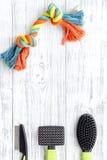 Strumenti di cura e governare di animale domestico con le spazzole sullo spazio di legno bianco di vista superiore del fondo per  Immagine Stock Libera da Diritti