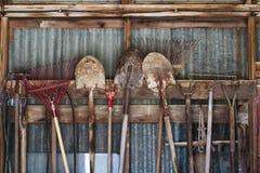 Strumenti di giardino che appendono in una fila in una tettoia immagini stock