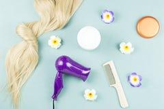 Strumenti di lavoro di parrucchiere, maschera di nutrizione ed estensioni dei capelli su fondo di legno blu Disposizione del pian fotografia stock