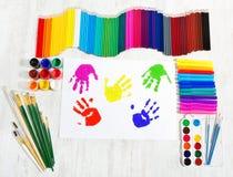 Strumenti di verniciatura, stampe della mano del bambino. Creatività fotografie stock