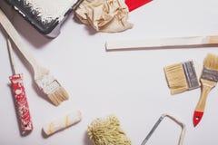 Strumenti di verniciatura utilizzati con le maniglie rosse coperte in pittura bianca calda Immagine Stock