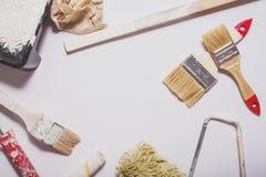 Strumenti di verniciatura utilizzati con le maniglie rosse coperte in pittura bianca calda presentata in una composizione su un f Immagine Stock