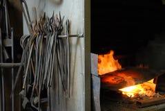 Strumenti e fuoco in una fucina Fotografia Stock Libera da Diritti
