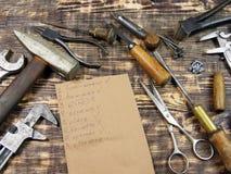 Strumenti e la lista degli strumenti sulla tavola Fotografia Stock