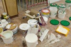 Strumenti e latte della pittura nella stanza per la verniciatura per il lavoro di riparazione Immagine Stock Libera da Diritti