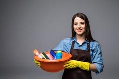 Strumenti e prodotti di pulizia della tenuta della giovane donna in secchio, isolato su grey Fotografia Stock