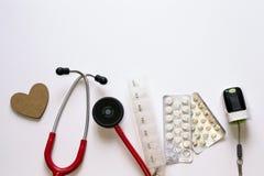 Strumenti medici su fondo bianco con copyspace per testo Cuore di legno, stetoscopio rosso pillole contenitore, bolle, impulso fotografia stock libera da diritti