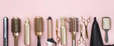 Strumenti professionali dell'apprettatrice dei capelli su fondo rosa con lo spazio della copia immagini stock libere da diritti