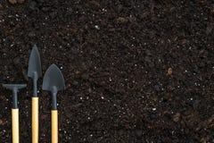 Strumenti, rastrello e pale messi di giardinaggio sulla terra nera del suolo con lo spazio della copia fotografia stock
