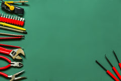 Strumenti sparsi per la riparazione di elettronica su un fondo verde Immagini Stock