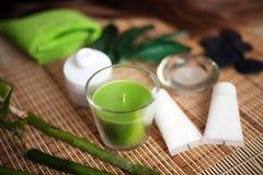Strumenti verdi della stazione termale con la candela e l'asciugamano su legno immagini stock libere da diritti
