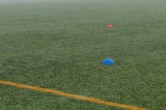 Strumento del cono per la formazione sull'erba artificiale nell'accademia di calcio fotografia stock libera da diritti