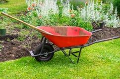 Strumento di giardinaggio davanti ad un letto di fiore immagine stock libera da diritti