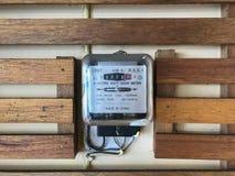 Strumento di misura del contatore elettrico di watt-ora sulla parete di legno immagini stock libere da diritti