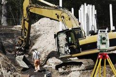 Strumento di rilevamento topografico, bulldozer e lavoratore fotografie stock