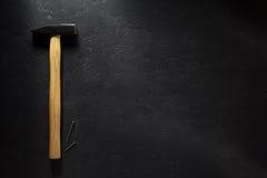 Strumento e chiodo del martello al nero Immagine Stock