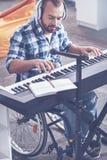 Strumento musicale di gioco disabile entusiasta nello studio di registrazione fotografia stock