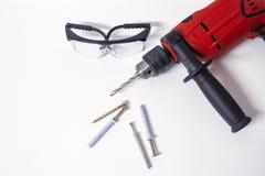 Strumento professionale per perforare Trapano elettrico con gli occhiali di protezione su un fondo del muro di mattoni fotografia stock