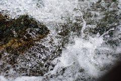 Strumień policzkował fala na kamieniu fotografia royalty free