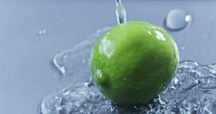 Strumień woda nalewa na zielonym wapnie na szarym szklanym tle Zwolnionego tempa 2k wideo shooted na 240 fps zdjęcie wideo