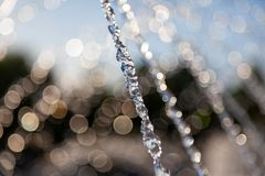 Strumień woda od fontanny w zamarznięty pozycji nalewać oddolny z pluśnięciami i round kroplami na tle zamazany fotografia stock