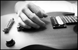 Strumming the Electric Guitar. Black and White upward view of hand playing the electice guitar Stock Images