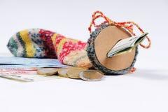 Strumpf für die Rettung mit Eurorechnungen und Euromünzen Stockbilder