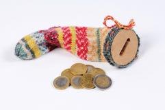 Strumpf für die Rettung mit Eurorechnungen und Euromünzen Stockfotos