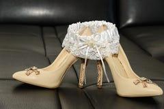 Strumpfband der Brautschuhe auf einer Ledercouch lizenzfreies stockfoto