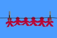 Strung Out. Line of Cut-out people strung on washing line Stock Photography