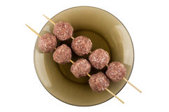 Strung on skewer meatballs in brown plate isolated on white Royalty Free Stock Photos