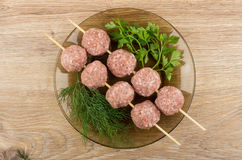 Strung on skewer meatballs with greens in brown plate. On wooden table. Top view Stock Photos