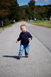 Struttin. One year old boy taking a walk on a rural road Royalty Free Stock Image