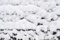 Struttura aerata di neve lanuginosa che si trova su un banco di legno Fondo immagini stock