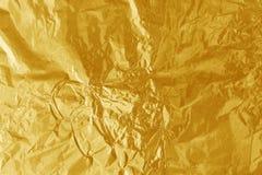 Struttura brillante della foglia della stagnola di oro, carta da imballaggio gialla astratta per fondo fotografie stock