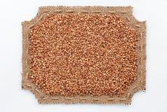 Struttura calcolata di tela da imballaggio con i grani del grano saraceno Fotografie Stock Libere da Diritti