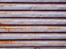 Struttura colorata urbana metallica con il modello orizzontale della ruggine sotto forma di strisce, ciechi Immagini Stock
