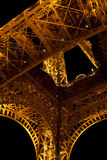 Struttura d'acciaio accesa giallo da sotto la torre Eiffel Fotografie Stock Libere da Diritti